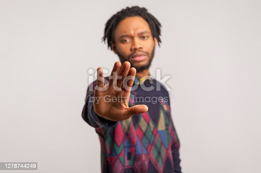 Worried african man with dreadlocks showing stop gesture with palm of his hand, concerned about bullying and domestic violence, need help. Indoor studio shot isolated on gray background