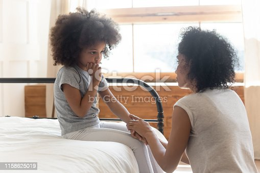 istock Worried african mother holding hand comforting sad little daughter 1158625019