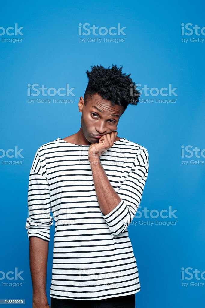 Worried afro american guy Portrait of worried afro american young man wearing striped top, looking at camera with hand on chin. Studio portrait, blue background. Adult Stock Photo