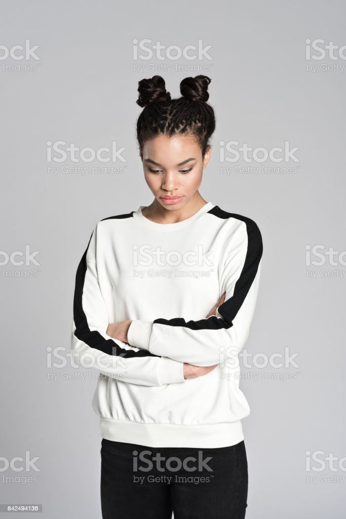 Worried afro american teenager woman Studio portrait of worried afro american teenage woman. Studio shot, grey background. 16-17 Years Stock Photo