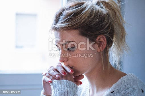 istock Worried and alone girl next to the window light 1053085302