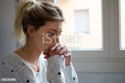 istock Worried and alone girl next to the window light 862282960