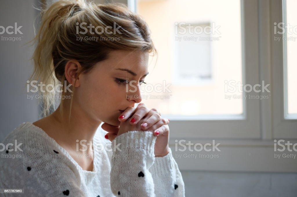 Orolig och ensam tjej bredvid fönster ljus bildbanksfoto