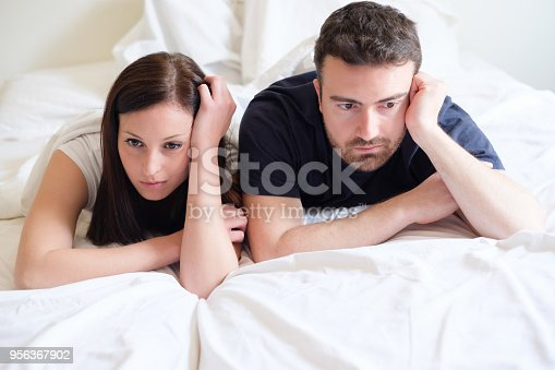 683664728istockphoto Worried and bored lovers couple after a fight lying in bed 956367902
