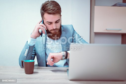 626916886istockphoto Worried and Exhausted Businessman Talking on Phone in his Office and Checking the Time 846096892