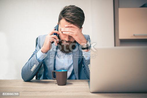 626916886istockphoto Worried and Exhausted Businessman Talking on Phone in his Office 833666288
