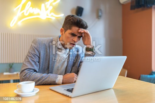 626916886istockphoto Worried and Exhausted Businessman working on a laptop 1051482376