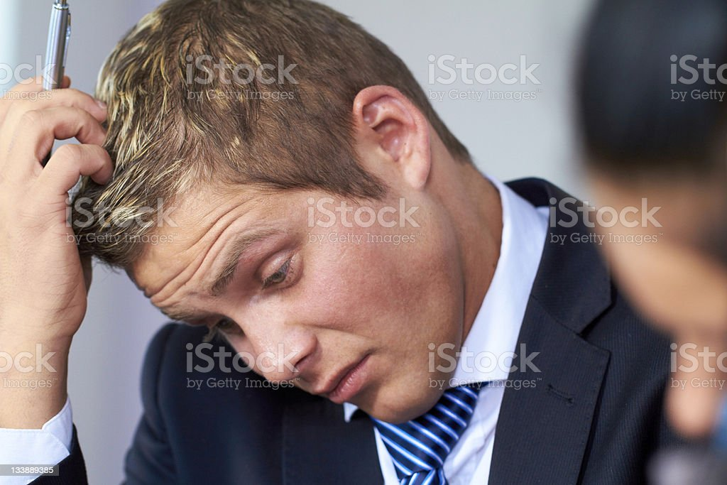 Worried and stressed young businessman scratch his head stock photo