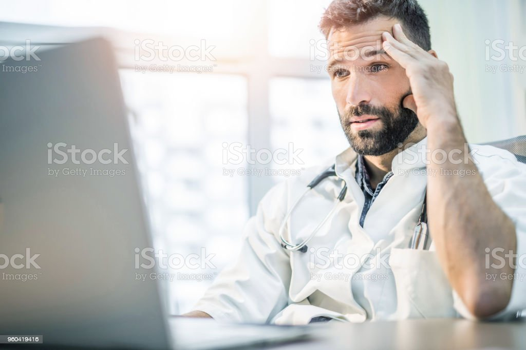 Worried and tired mid adult male doctor reading medical results on his laptop. stock photo
