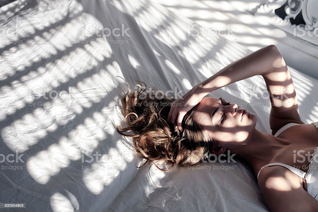 Worried and tired woman lying on bed in the morning royalty free stockfoto