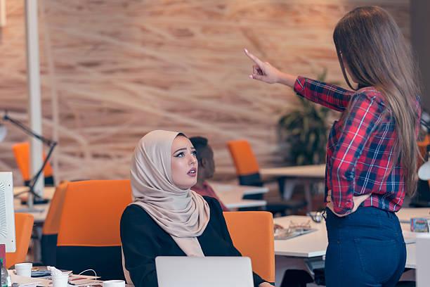 worried arabic businesswoman wearing hijab receiving a notification - kündigung arbeitsvertrag stock-fotos und bilder