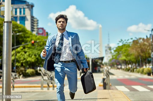 Young Hispanic businessman in full suit with briefcase hurrying down city street on way to appointment.