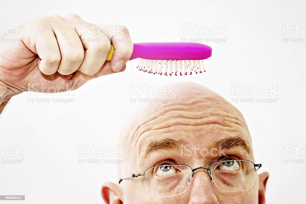 Worried bald man eyes hairbrush: a pointless tool! stock photo