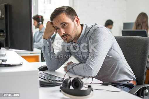 istock Worried beard man looking at computer screen in office 932342408