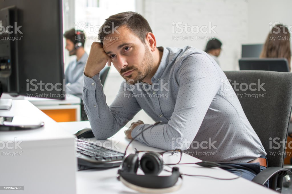 Worried beard man looking at computer screen in office stock photo