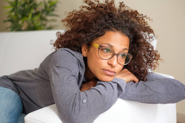 Worried black woman at home alone stock photo