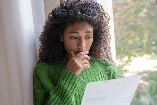 Worried black woman reading a layoff notice at home stock photo