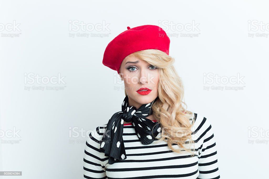 Worried blonde french woman wearing red beret Portrait of worried blonde woman in french outfit, wearing a red beret, striped blouse and neckerchief, looking at camera. Adult Stock Photo