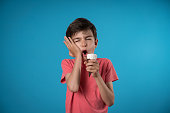 Worried boy experiencing tooth ache over colored background