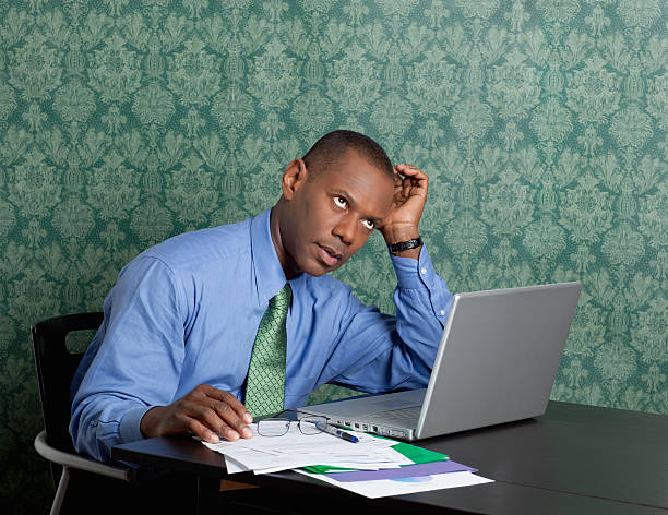 Worried business man with laptop and documents at work Portrait of a worried business man with laptop and documents at work rolling eyes stock pictures, royalty-free photos & images