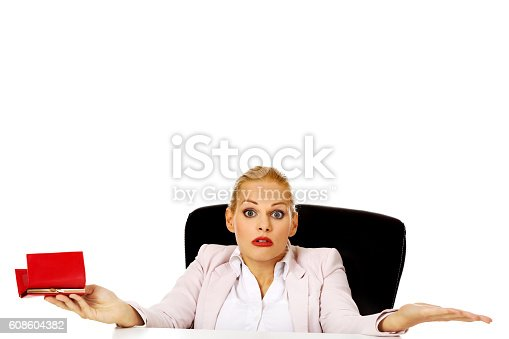 istock Worried business woman sitting behind the desk with empty wallet 608604382