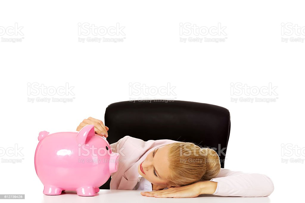 Worried business woman with a piggybank behind the desk stock photo
