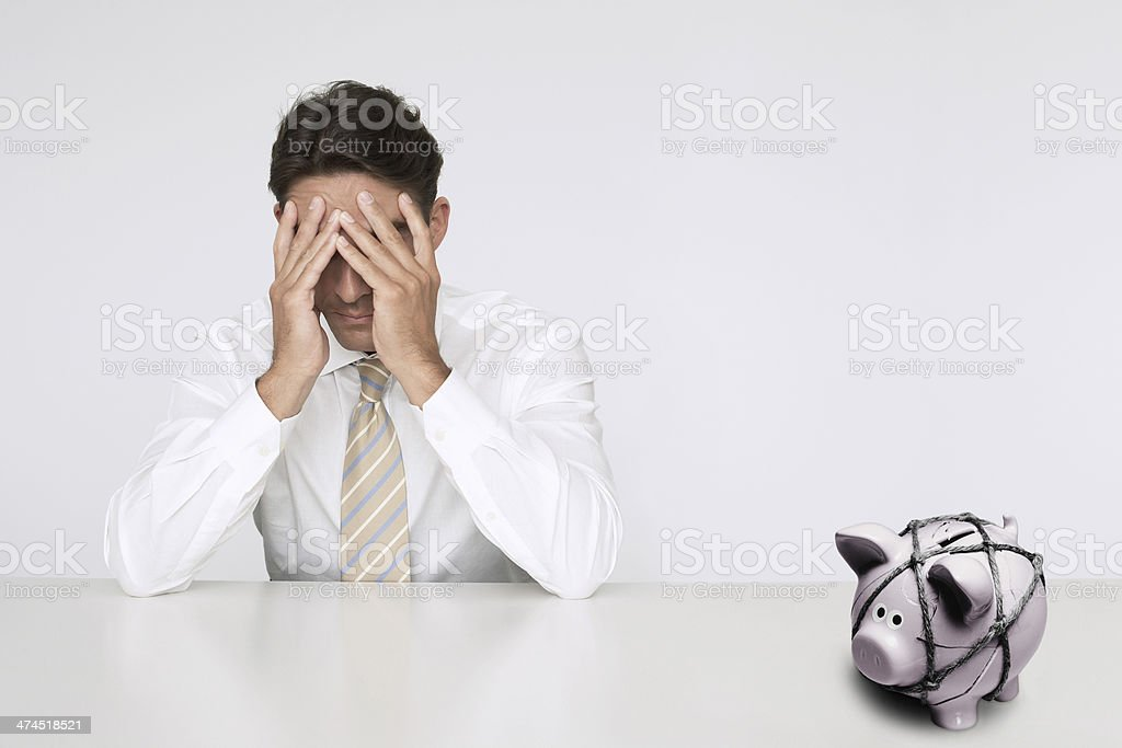 Worried businessman at table with trapped piggy bank stock photo