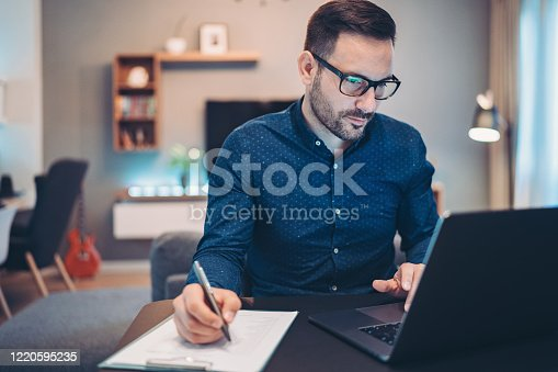 Businessman using laptop and doing paperwork at home