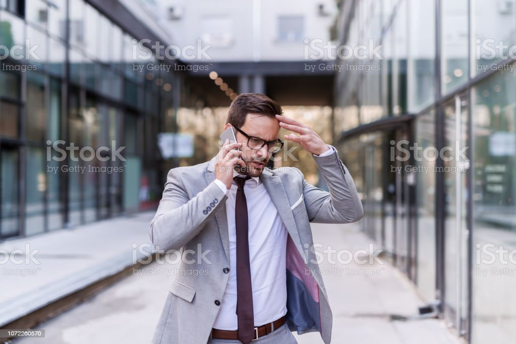 Worried businessman dressed in formal wear using smart phone for a...