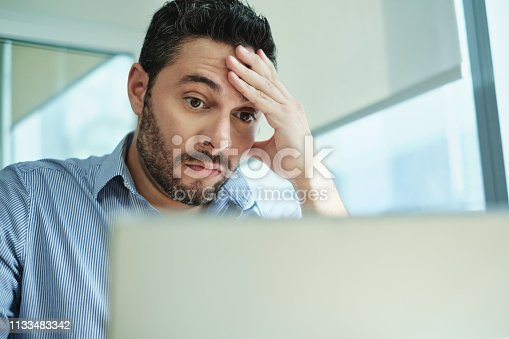 Upset business man working with laptop computer in office, feeling stressed and anxious for possible data loss. Adult Hispanic executive under stress at work for technology problems and software pc virus.