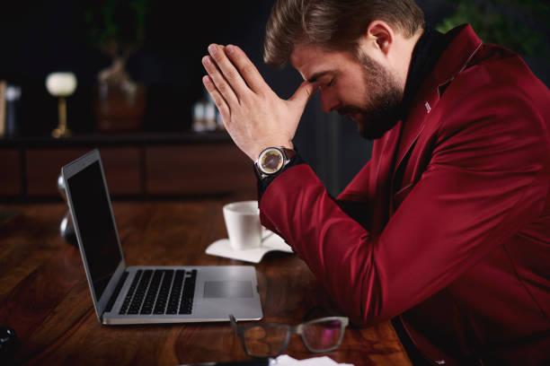 besorgt geschäftsmann in seinem büro zu beten - migräne vorbeugen stock-fotos und bilder
