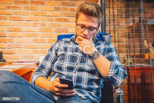 626916886istockphoto Worried businessman reading a text message on cell phone in office 695047794