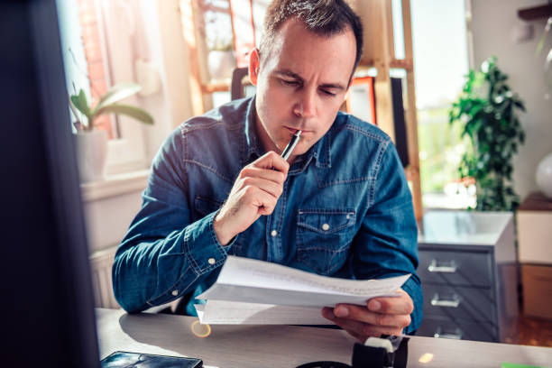 Worried businessman reading mail at office stock photo