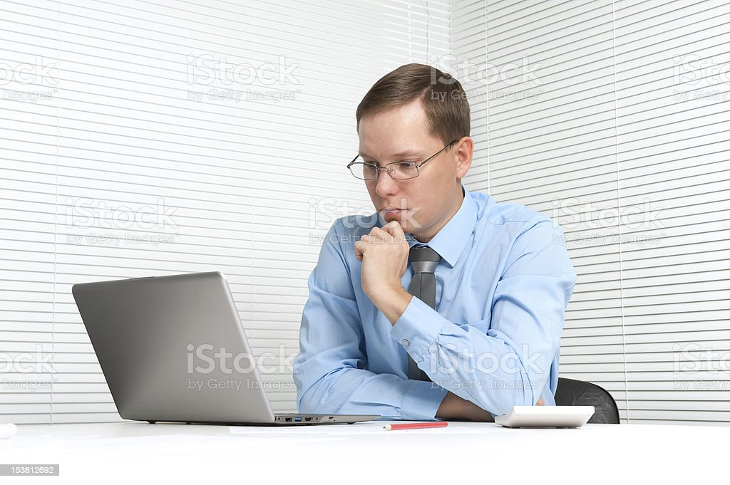 worried businessman sitting at desk with laptop royalty-free stock photo