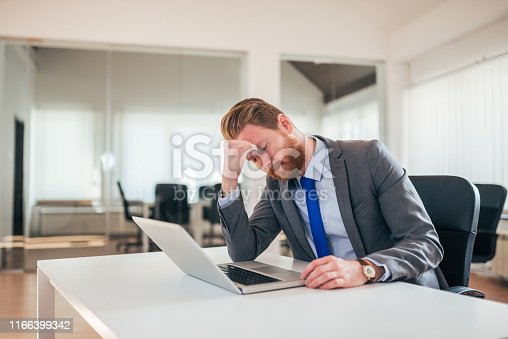 Worried businessman sitting at office desk with laptop.