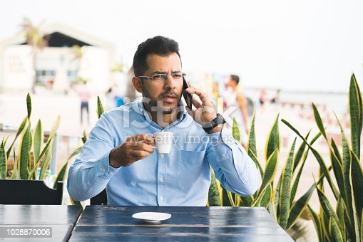 626916886istockphoto Worried businessman talking on phone in a coffe shop 1028870006