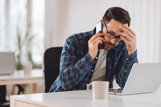 Worried businessman talking on phone stock photo
