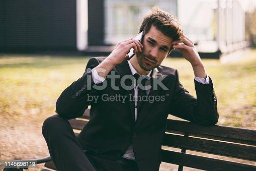865714662 istock photo Worried businessman using phone 1145698119