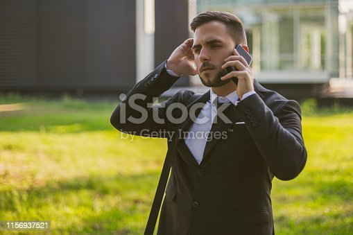 865714662 istock photo Worried businessman using phone 1156937521