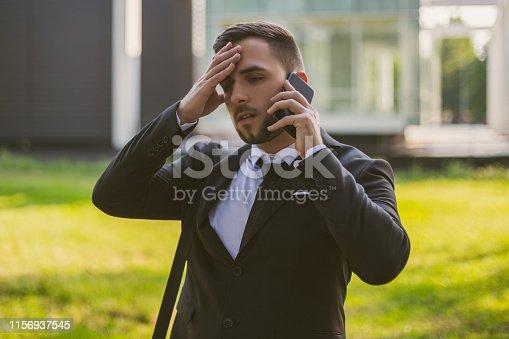 865714662 istock photo Worried businessman using phone 1156937545