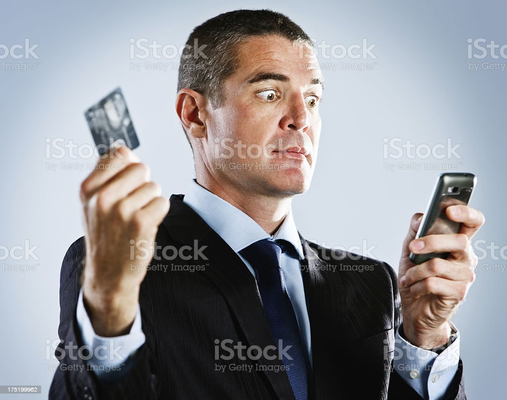 Worried businessman with cellphone and bank card: no more credit stock photo