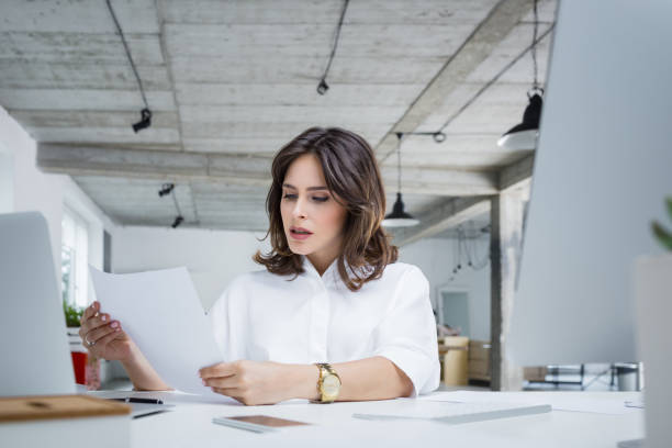 Worried businesswoman reading a document stock photo