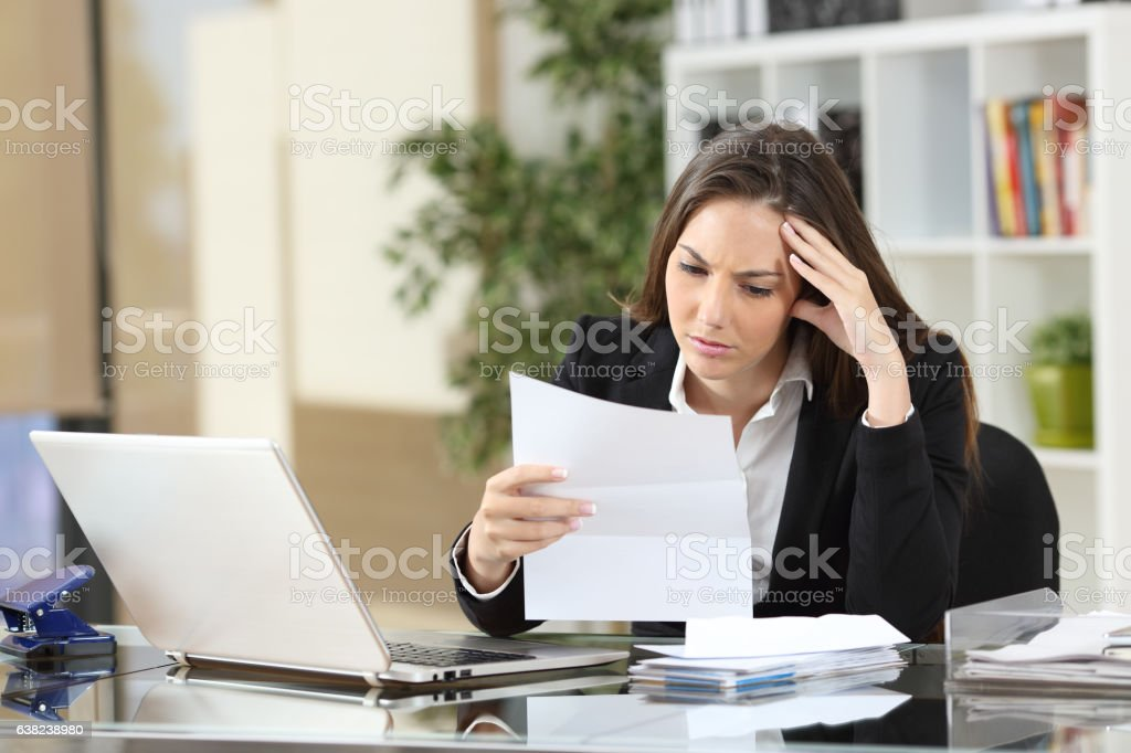 Worried businesswoman reading a notification stock photo