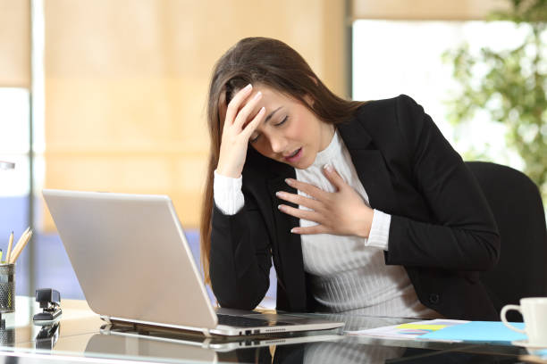 Worried businesswoman suffering an anxiety attack stock photo