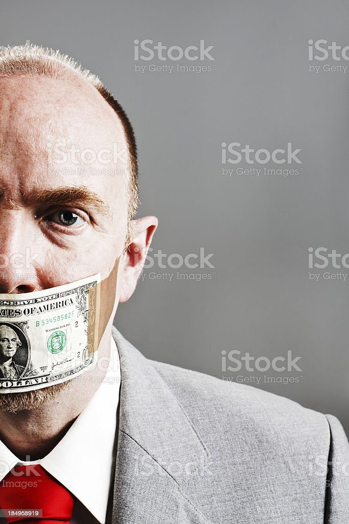 Worried confused mature businessman is gagged by US dollar bill stock photo