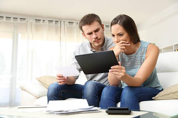 worried couple checking bank account online - кредит и кредитные карты стоковые фото и изображения
