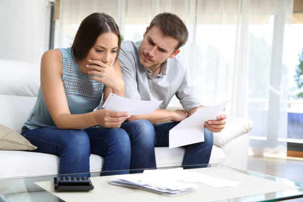 Worried couple checking receipt sitting at home stock photo