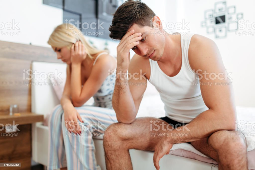 Worried couple having problems in bedroom stock photo