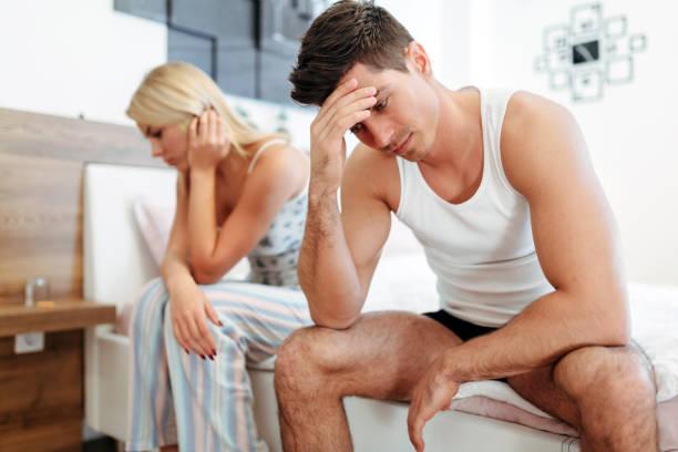 Worried couple having problems in bedroom stock photo