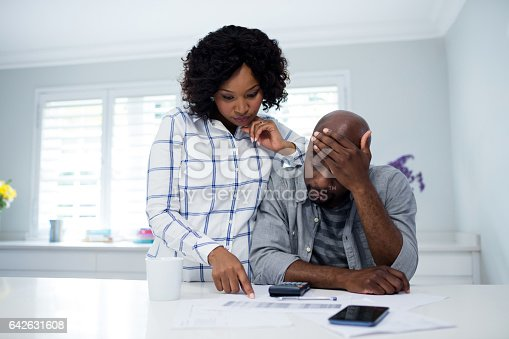 istock Worried couple interacting while checking the bills 642631608